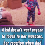 A kid doesnt want anyone to touch to her maracas